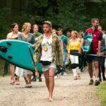 Teilnehmer laufen mit Kursleiter zum Kanusee bei SOMMERJUNG, dem Ferienlager für Erwachsene